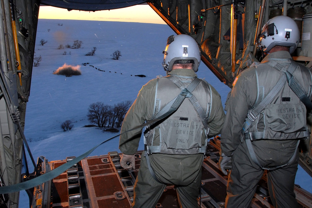Loadmasters from the Wyoming Air National Guard watch a one-ton hay bale land near a herd of cows during an emergency feeding mission Jan. 3 caused by a snowstorm that hit the area in southeastern Colorado. (U.S. Air Force photo/Senior Master Sgt. John Rohrer)