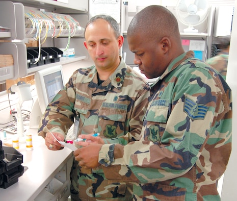 Maj. Gabriel Florit, 23rd Medical Group pharmacist, and Staff Sgt. Kenny Warren, 23rd MDG pharmacy technician, verify the details of a prescription order at the Moody pharmacy recently. Major Florit immigrated from Cuba when he was 14 years old and later enlisted in the Army. He later earned a college degree and served as an officer in the Navy before entering the Air Force. (U.S. Air Force photo by Tech. Sgt. Parker Gyokeres)