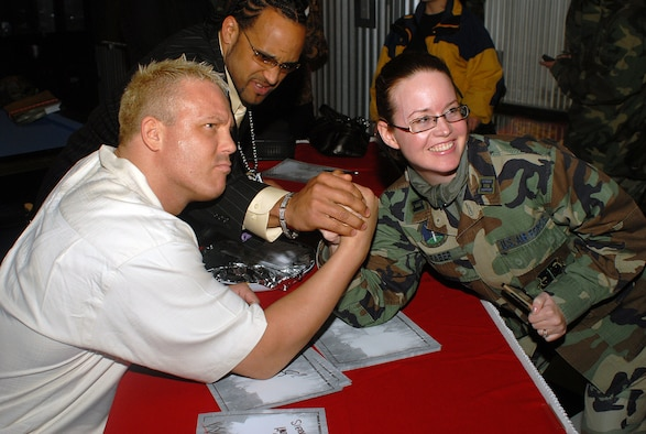 "Capt. Lisa Faber, 314th Logistics Readiness Squadron, arm wrestles Mr. Ken Kennedy, a World Wrestling Entertainment wrestling superstar, as ""MVP,"" Montel Vontavious Porter, tries to help her secure a win. The two wrestlers stopped at J.R. Rockers Jan. 16 to show their support to base Airmen before heading to ALLTEL Arena to wrestle live on ""SmackDown."" (Photo by Airman 1st Class Nathan Allen)"