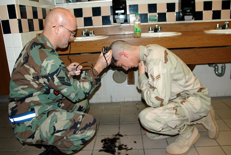 EGLIN AIR FORCE BASE, Fla. – Airman 1st Class Jacob Hoffman, 728th Air Control Squadron surveillance technician, receives a hair cut from Master Sgt. James Pennington, 728th ACS assistant superintendent of operations prior to deploying to Southwest Asia in support of Operation Iraqi Freedom Jan. 15. (Air Force photo/by Staff Sgt. Phillip O. Butterfield)
