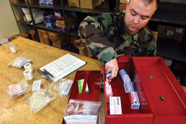 MCCHORD AIR FORCE BASE, Wash.-- Airman 1st Class Brantley Day, 62nd Aerial Port Squadron, uses a checklist in Bldg. 1419 to ensure first aid kits are complete prior to being transported to various aircraft.(U.S. Air Force photo/Abner Guzman)