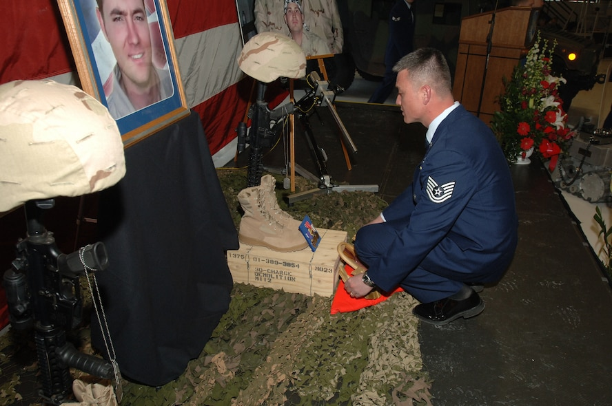 Tech. Sgt. Robert Hood, 775th Civil Engineer Squadron Explosive Ordnance Disposal Flight, puts finishing touches on a memorial display to the three Hill Airmen who were killed in Iraq Sunday.