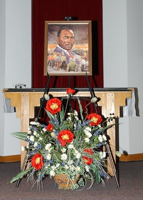 A painting of Dr. Martin Luther King Jr. and a floral tribute displayed on the altar helped bring focus to the members of Team Lackland who came together for a commemorative service Jan. 11 at Freedom Chapel honoring the late Dr. King. Guest speaker for the service was a longtime Lackland Air Force Base, Texas, choir director, Bradley Scott, Ph.D., senior education associate for the Intercultural Development Research Association. (USAF photo by Alan Boedeker)