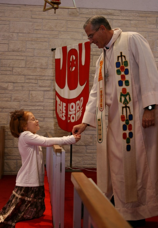 Chap. Fulton serves his granddaughter Morgan,8, her first communion during his first service at St. Paul's Lutheran Church after his deployment. (Courtesy Photo)