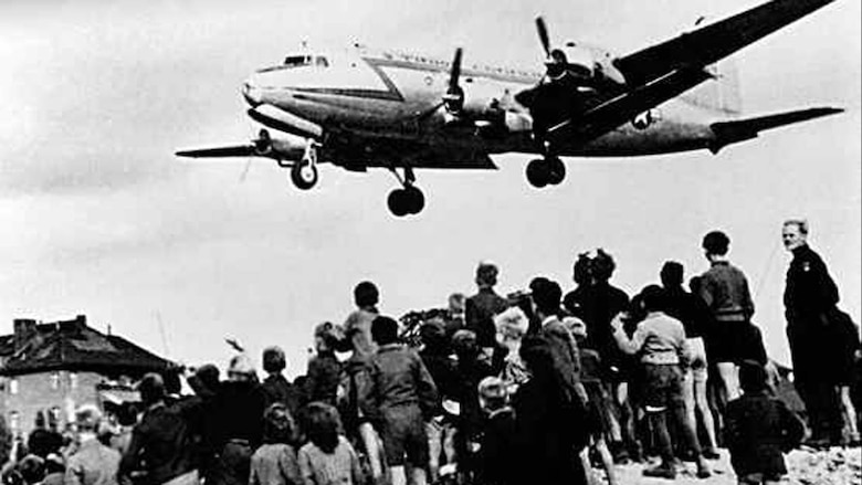 West Berliners watch as a U.S. cargo plane delivers desperately needed supplies during the Berlin Airlift.  (File photo)