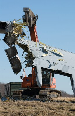 A contractor removes portions from the April 3, 2006 C-5 mishap aircraft this week at Dover Air Force Base, Del. (U.S. Air Force photo/Roland Balik)