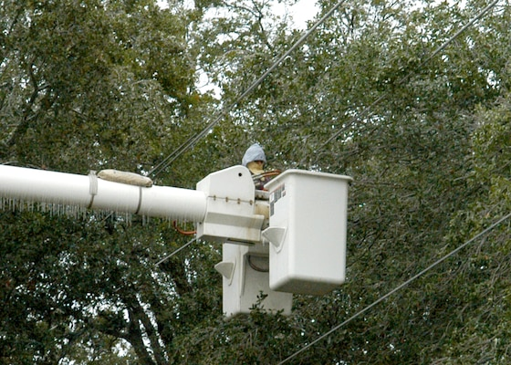 "Guadalupe Montana, a 37th Civil Engineer Squadron exterior foreman, stretches from a lift bucket to cut an ice-laden tree limb responsible for a two-hour power outage starting around 10 a.m. Jan. 17 on the southern training side of Lackland Air Force Base,Texas. Mr. Montana said the limb, near Bldg. 5570 on Selfridge Avenue between Hughes and Walker Avenues, pushed a primary power line into another line, causing a ""big ball of fire"" before the short tripped a circuit breaker. The winter storm resulted in the base being closed for Jan. 16 and 17. (USAF photo by Alan Boedeker)"