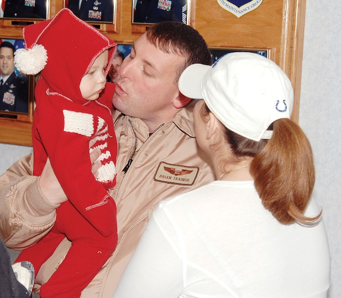 Capt. Brian Trainor, an evaluator and electronic warfare officer with the 38th Reconnaissance Squadron, is greeted by son Peyton, 10 months, and his wife, Jeanine. The captain was one of approximately 130 Team Offutt members who returned to the Heartland in time for the holiday season. U.S. Air Force Photo by Josh Plueger