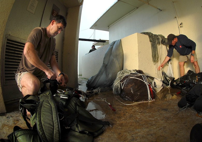 Master Sergeant Rich Carroll and Senior Airman Chris Harding from the 31st Rescue Squadron, Kadena Air Base, Japan, rinse off the salt water from parachutes and clean up gear after participating in a weekly training exercise Jan. 16.  (U.S. Air Force photo/Airman 1st Class Kelly Timney)