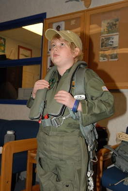 Matthew McLean tries on flight gear used by F-15 pilots during his visit to the 95th FS.