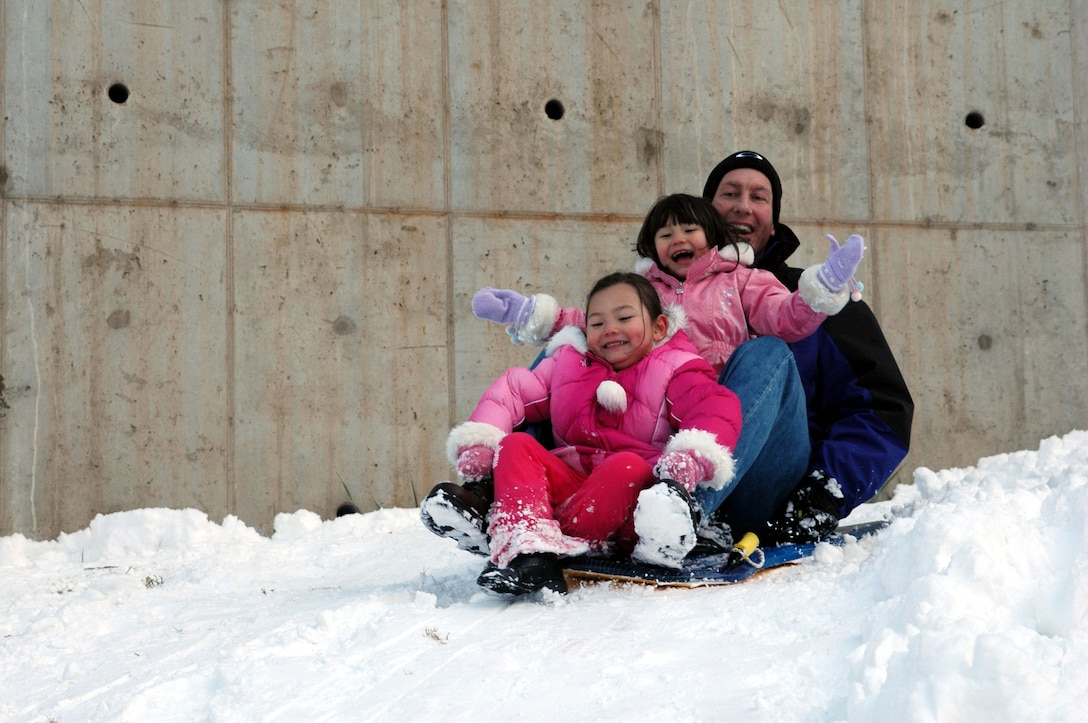 OSAN AIR BASE, Republic of Korea --  Lt. Col. Daren Sears and daughters Tara, 5, and Brooke, 3, enjoy a day of sledding on a hill near Seoraksan Tower 211 Sunday following Saturday's late night snowstorm which covered the base with 6.25 inches of snow. The region receives an average of 15 inches of snow between December and March. (U.S. Air Force photo by Tech. Sgt. Michael O'Connor)