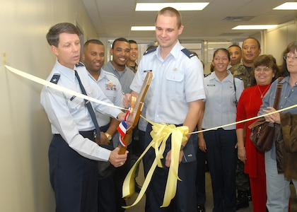 Brig. Gen. Darrell Jones uses a giant pair of scissors to cut a ribbon to dedicate the new Lackland Air Force Base Tax Center in the Carswell Administration Building, Bldg. 9050, Suite 3700. Standing beside General Jones, then the 37th Training Wing commander, is 1st Lt. Eric Adams, officer in charge of the center. The center will open Feb. 5, 2007. The building, at 1700 Carswell Ave., is near clothing sales on Hughes Avenue at Kirtland Street. Hours of operation will be 8-11 a.m. and 1-3 p.m. Monday through Thursday. Appointments are required for all but basic military trainees and technical school students by calling 671-7983 starting Monday. Also, each unit has at least one tax advisor ready to assist with federal income tax returns.