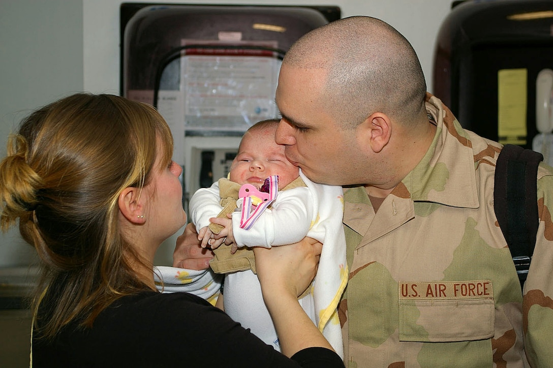 Senior Airman Michael Rios gives his 7-week-old daughter, Alleigh, and wife, Cristy, a kisses goodbye at the passenger terminal before leaving on a deployment to Southwest Asia Jan. 23 from Royal Air Force Mildenhall, England. Airman Cardenas is assigned to the 100th Civil Engineer Squadron. (U.S. Air Force photo/Karen Abeyasekere)