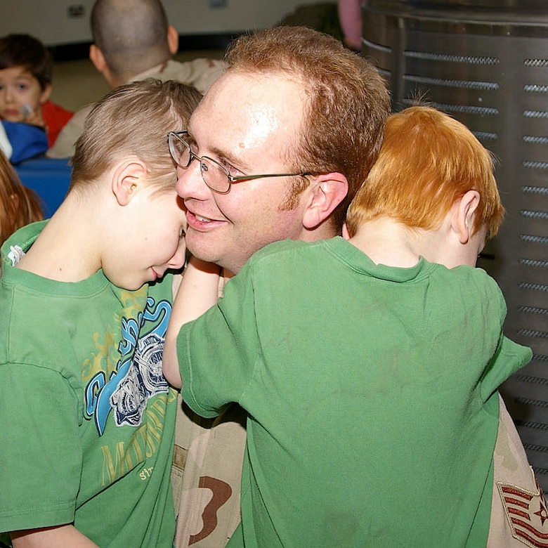 Tech. Sgt. Gregory James gives goodbye hugs to sons Dalen, 10, and Tamner, 7, at the Royal Air Force Mildenhall, England, passenger terminal Jan. 23 before leaving on a deployment to Southwest Asia. Sergeant James is assigned to the 423rd Civil Engineer Squadron at RAF Alconbury, England. (U.S. Air Force photo/Karen Abeyasekere)