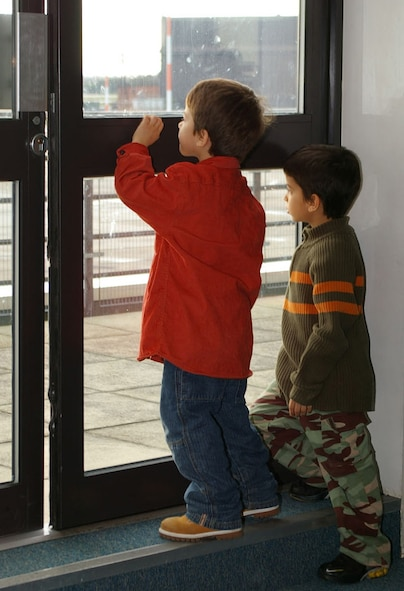 Elijah Cardenas, 5, and his brother André, 7, 100th Civil Engineer Squadron family members, gaze out onto the runway at RAF Mildenhall. They watch the plane outside being prepared for the deployment that dad, Senior Airman Miguel Cardenas, is preparing to leave on, to Southwest Asia. (U.S. Air Force photo by Karen Abeyasekere)