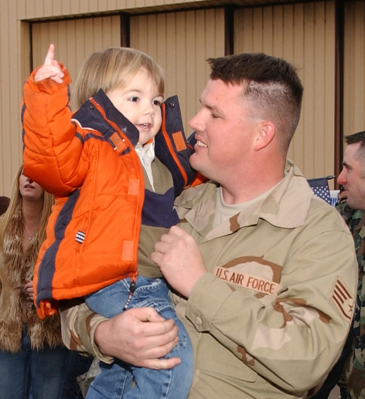 Staff Sgt. Nicholas Asbury, 27th Equipment Maintenance Squadron, holds his son at the flightline shortly after returning to Cannon Air Force Base, N.M. via a chartered jet Jan. 18. Sergeant Asbury was one of nearly 300 Airmen who returned on the flight after serving in Iraq for four months. (Air Force photo/Tech. Sgt. Scott McKay)