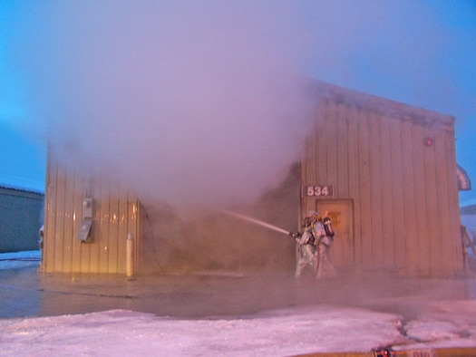 EIELSON AIR FORCE BASE, Alaska -- Firefighters battle a fire at the recylcing center Jan. 18. The recycling center's pelletizer, a piece of equipment designed to process used paper and convert it into pullets to burn in Eielson's power plant, was the source of the fire.