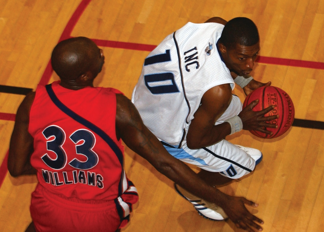 OSAN AIR BASE, Republic of Korea --  Janus Williams, Defender 33, tries to stop a Yongsan player as he attempts to drive to the hoop during Wednesday's final game. (U.S. Air Force photo by Airman Ruthann Holcomb)