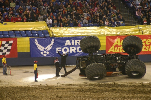 Monster Mutt driver Bobby Z emerges from his overturned 1951 Mercury shelled monster truck and poses with thumbs up in front of the Air Force banner at the Tacoma Dome Jan. 12 in Tacoma, Wash. The driver couldn't keep the 66-inch tires under the precious pooch while navigating a sharp turn in the freestyle competition of the event.  Recruiters from the 361st Recruiting Squadron were on hand over the weekend passing out Air Force literature and promotion items and answering questions to those enquiring more on life in the Air Force.  (U.S. Air Force photo by Tech. Sgt. Chuck Marsh)