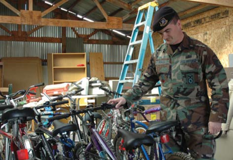 Tech. Sgt. George F. Roach, a security forces member here and Vice President of AFSA's Tucson chapter, steadies one of the 26 bicycles donated to Esperanza En Escalante, a local transitional housing program for homeless veterans.