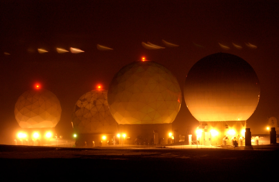"At Detachment 3, four ""golf ball"" protective covers that house satellite dishes are viewed during the darkness Jan. 25 at Thule Air Base, Greenland. Thule AB Airmen with two major space missions support the Air Force Space Command mission. (U.S. Air Force photo/Michael Tolzmann)"