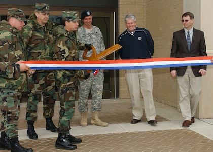 Brig. Gen. Darrell Jones, then the 37th Training Wing commander at Lackland Air Force Base, Texas, prepares to cut a ribbon Jan. 22, 2007, to dedicate a new 300-room, 600-man dormitory for 343rd Training Squadron security forces students. With the general, from left, are Col. Eric Beene, commander of the 37th Mission Support Group; Lt. Col. Mike Kelly, deputy commander of the 37th Training Group; Maj. Ray Walser, Lackland resident engineer for the Army Corps of Engineers; Tim Chadwick, president of MW Builders of Texas Inc.; and John Heye, deputy civil engineer for the 37th Civil Engineer Squadron. MW Builders constructed the dorm at the north end of Carswell Avenue, along with a new dining facility that opened Jan. 3 on Lackland Training Annex, under a single $33.4 million military construction contract. (USAF photo by Alan Boedeker)