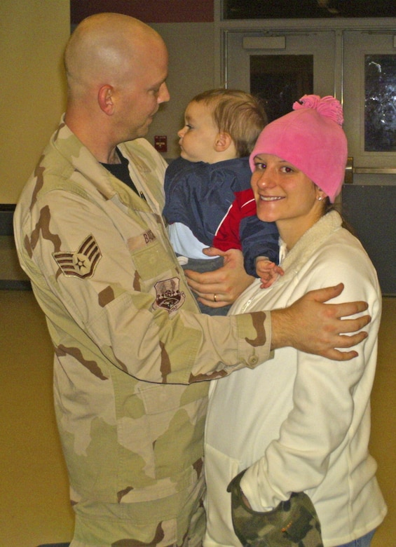 After more than 36 hours on a chartered flight, Staff Sgt. Thomas Badgero is greeted by wife, Rose, and son, Hunter, Jan. 23 at the Joint Mobility Complex at Eielson Air Force Base, Alaska. Sergeant Badgero is assigned to the 354th Logistics Readiness Squadron. (U.S. Air Force photo/Senior Airman Aaron Bonifazi)