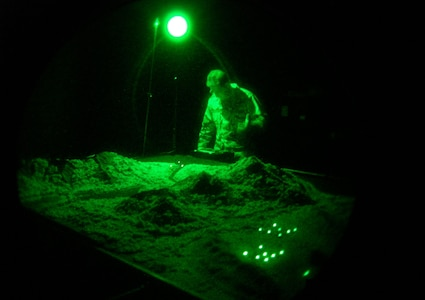 """Capt. Tom Massa, Air Force Night Vision Goggle Academic Instructor Course director, adjusts the lighting on the terrain board (a scale model of desert mountain urban environments) in the """"nite lab"""" to demonstrate the effects of shadows, illumination and contrast on NVG visual performance. (U.S. Air Force photo by Capt. Alex Ramos)"""