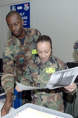 Left, Senior Airman Evans Opoku and Staff Sgt. Veronique Blier, 66th Medical Group, double check deployers' records as part of the January Base Readiness Exercise. Hanscom practiced  deploying a large group in preparation for the upcoming Operational Readiness Inspection in June. (US Air Force Photo by Jan Abate)