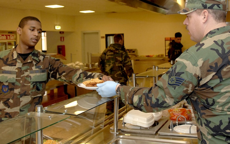 Staff Sgt. Troy Anderson, 120th FW food service craftsman, serves lunch to an Airman at the La Dolce Vita Dining Facility.  (Photo by Airman 1st Class Michael Dorus)