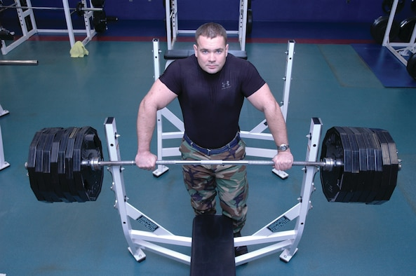 OSAN AIR BASE, Republic of Korea --  Staff Sgt. Michael Schwanke stands behind a bar with 675 pounds, the same amount of weight he lifted at the 8th Army powerlifting competition. In order to get that much weight on a bar, 14 45-pound plates were added. Through years of workout, he has developed a 47 inch chest, 18.5 inch biceps and 29.5 inch thighs. (U.S. Air Force photo by Tech. Sgt. Michael O'Connor)