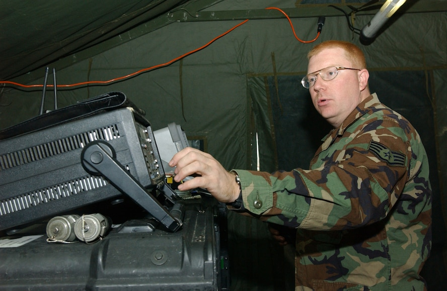 OSAN AIR BASE, Republic of Korea --  Staff Sgt. Erik Knippa, 607th Combat Communications Squadron, monitors the computer system inside the deployed tactical satellite shop Dec. 1. (U.S. Air Force photo by Senior Airman Eunique Stevens)