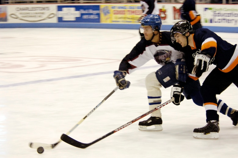 Christopher Pace, Air Force forward, battles for control of the puck with a Coast Guard player during the game. The Coast Guard beat the Air Force team 6-3, however, Air Force qualified for the Stingrays Military Cup to be held Feb. 17 at 3 p.m. at the North Charleston Coliseum against the Navy team. (U.S. Air Force photo by Staff Sgt. Ricky Bloom)