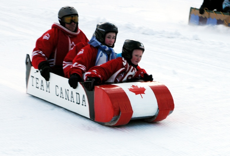Julie King, Kayla King, Alexandra Ashcroft and Canadian Warrant Officer Les Deviller, NORAD/NORTHCOM J6, speed down Keystone's Discovery Slope Jan. 27, during the cardboard derby contest. The Crazy Canucks' sled, made only of cardboard and tape, won the fastest sled category. (U.S. Air Force photo by Steve Brady)