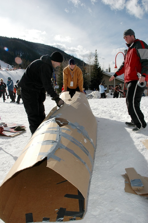 Cardboard derby entrant 2nd Lt. Zach Bass (left), deputy flight commander, 90th Services Squadron, F.E. Warren Air Force Base, helps prepare his team's derby entry Jan. 27 at Keystone. Helping Lieutenant Bass are his friends Michael Hays (center) and Carl Seiley, from Ohio. (U.S. Air Force photo by Steve Brady)