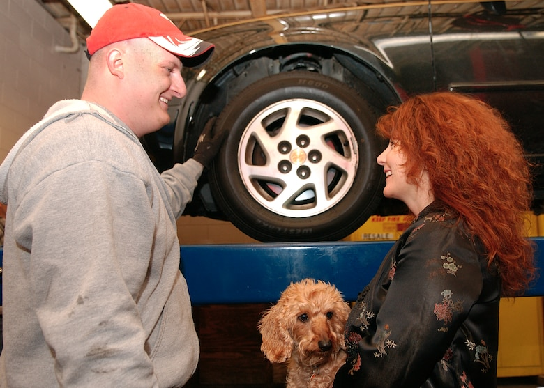 Staff Sgt. Andrew Wettstein, 314th Logistics Readiness Squadron, goes over a vehicle inspection with Kathy Atkins, wife of Lt. Col. Joseph Atkins, 314th Mission Support Squadron commander, and their dog, Frankie, at the Auto Hobby Shop Jan. 27. LRS members volunteered their Saturday to inspect vehicles for deployed or deploying Airmen's family members. Another free inspection is 9 a.m.-5 p.m. Feb.3 at the hobby shop. Contact your sponsor's first sergeant or call 987-6996 for an appointment. (Photo by Airman 1st Class Steele Britton)