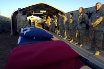 Airmen deployed to the 332nd Air Expeditionary Wing unfold an American flag at the Hero's Highway Ceremony Jan. 22 at Balad Air Base, Iraq. The flag is posted on the inner roof a tent so injured troops can look up and know they are in an American area when brought in on litters seeking medical treatment. The medical group raised injured troops' survival rate to 98 percent. (U. S. Air Force photo/Airman 1st Class Nathan Doza)