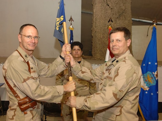 Kirkuk Regional Air Base, Iraq -- Air Force reservists Lt. Col. Tom Kuepper (right) deployed from the 445th Civil Engineer Squadron at Wright-Patterson AFB, Ohio receives the 506th Expeditionary Civil Engineer Squadron guidon from Col. Gregory Schwab (left) 506th Air Expeditionary group commander at Kirkuk RAB, Iraq on January 14. Senior Master Sgt. Lisa Rodriguez (center) is from the 445th Airlift Wing deployed as 506th Civil Engineer First Sergeant. More than 60 civil engineers from the 445th CES deployed to Kirkuk, Iraq to support the Global War on Terrorism (U.S. Air Force/SrA Bradley Lail).