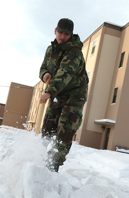 EIELSON AIR FORCE BASE, Alaska -- 354 Civil Engineer Squadron's Airman First Class Catlin Goodrich breaks away frozen ice in front of his Dormitory on Jan 30. A1C Goodrich is on Bay Orderly this week which consists of keeping the inside and outside of the dormitory in clean and working order. During the winter a lot of the time is spent shoveling snow to make safer paths to walk on.  (U.S. Air Force photo by Airman Christopher Griffin)