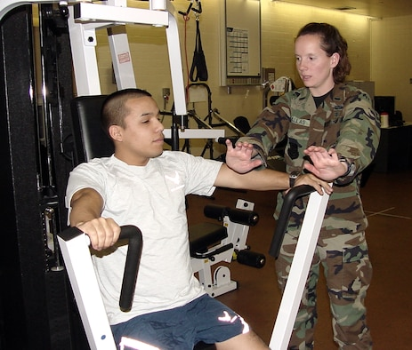 1st Lt. Elissa Ballas, 60th Surgical Operations Squadron physical therapist, demonstrates proper body and weight lift positioning with Airman 1st Class Vicente Rodriguez, 60 MSGS physical therapy technician. (U.S. Air Force photo by Jim Spellman)