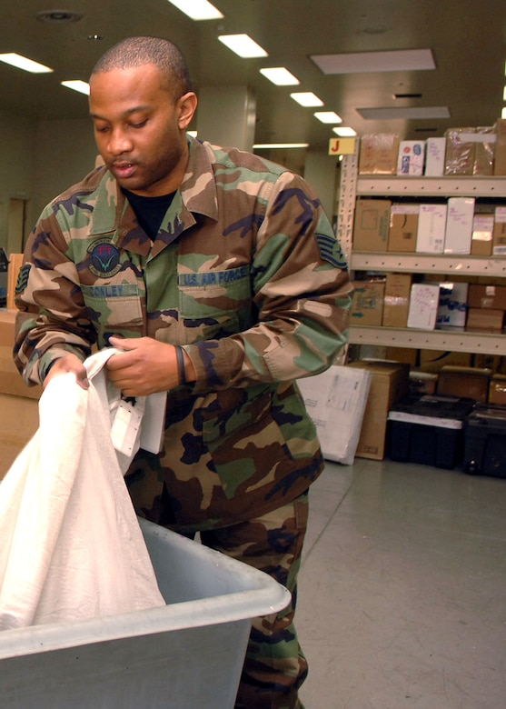 Staff Sgt. Anthony Conley unloads mail into a bin Jan. 30 at the post office on Yokota Air Base, Japan. Yokota AB receives approximately 5,000 individual letters and 500 parcels daily. Sergeant Conley is assigned to the 374th Communications Squadron. (U.S. Air Force photo/Senior Airman Veronica Pierce)