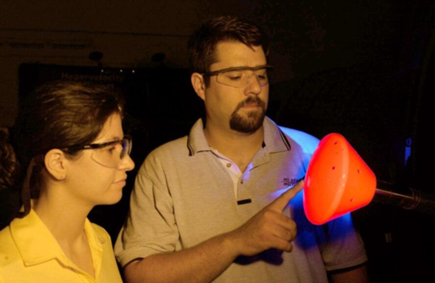 University of Maryland graduate student Inna Kurits and Tunnel 9 ATA project engineer Joe Norris examine the illuminated TSP coating on the NASA CEV model prior to a run. (U.S. Air Force photo)
