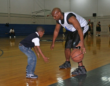 Angelo Baxter from the 314th Military Intelligence Battalion teaches dribbling to his son Elisha during half time Jan. 25 at the Chaparral Fitness Center. (Photo by Army Spc. Tim Luukkonen)