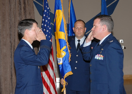 Brig. Gen. Darrell Jones, commander of the 37th Training Wing, left, returns the salute of Col. Tim Halligan as the colonel assumes command of the newly reactivated 37th Medical Group during a formal ceremony Jan. 25 at the Gateway Club on Lackland Air Force Base, Texas. Chief Master Sgt. Bob Rubio stands behind them with the group flag. (USAF photo by Robbin Cresswell
