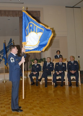 Chief Master Sgt. Noble Lisenbee, superintendent of the newly formed 59th Dental Training Group, brings the group's flag to a vertical position after unfurling it Jan. 25, 2007, at the Gateway Club on Lackland Air Force Base, Texas. Seated are (from left) Brig. Gen. Darrell Jones, then the 37th Training Wing commander, Brig. Gen. David Young, then the 59th Medical Wing commander, Col. Tim Halligan, then the commander of the newly reactivated 37th Medical Group, and Col. Don Sedberry, then the 59th Dental Training Group commander. (USAF photo by Robbin Cresswell)