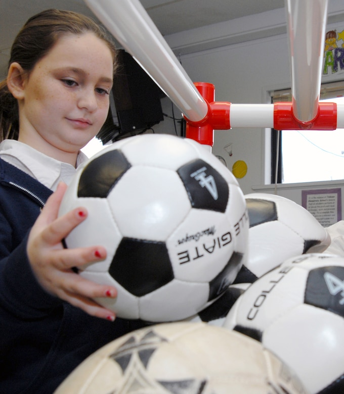 "Christy Hawking, 10, contributes to Tolleson Elementary School's donation of soccer balls for Djibouti children Jan. 31. Christy has already made a donation of 14 soccer balls to the schools collection box. The school hopes to collect at least one soccer ball per student to ""Operation Play,"" donating more than 300 altogether. (Photo by Staff Sgt. Jonathan Pomeroy)"