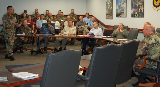 Lt. Col. Steven Albrecht, ESOHCAMP team chief, briefs wing leadership on the results of this year's internal Environment, Safety, Occupational Health Compliance Assessment and Management Program assessment. (U.S. Air Force Photo/Staff Sgt. Chris Powell)