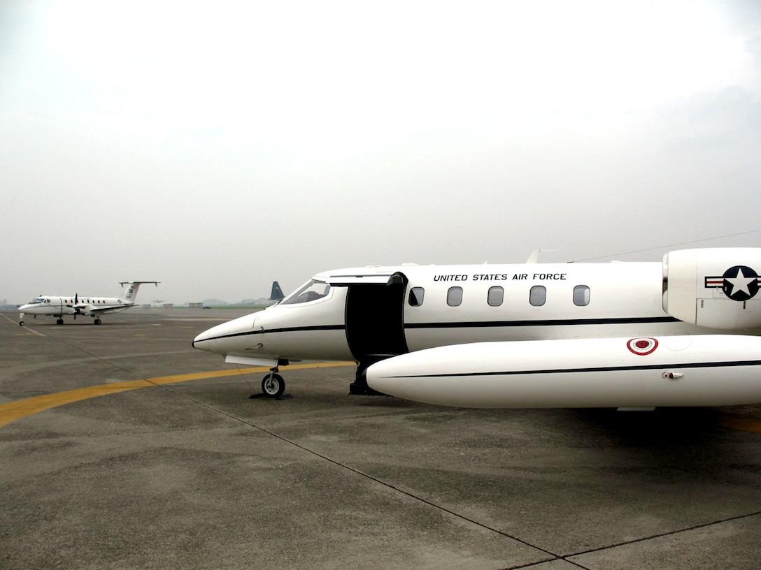 The C-12J Huron (left) arrives as the C-21 transport jet prepares to leave after serving for 21 years June 29 on Yokota Air Base, Japan. The C-12 is roomier than its predecessor, and has the ability to carry more people and land in more remote areas. (U.S. Air Force photo/Navy Seaman A.C. Rainey)