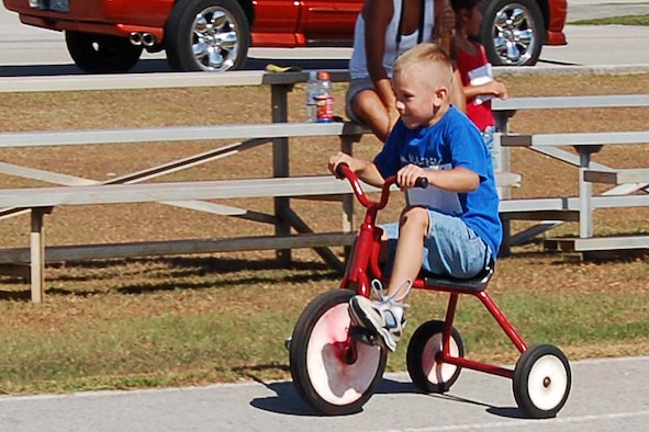 Vinny Gemmiti pedals furiously and wins the tricycle event at the family track day. (U.S. Air Force Photo/Airman 1st Class Carissa Morgan)