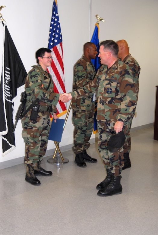Col. Bryan Gallagher (right), 95th Air Base Wing commander, presents two Airmen with their next stripe at the Security Forces Squadron headquarters building Monday. Airmen 1st Class Brooke Garton (left) and Mark Smith (center), 95th SFS security police, were awarded the rank of Senior Airman below the zone. (Photo by Airman Mike Young)